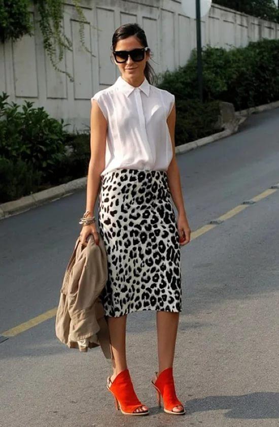 Женщина в белой блузке и леопардовой юбке.