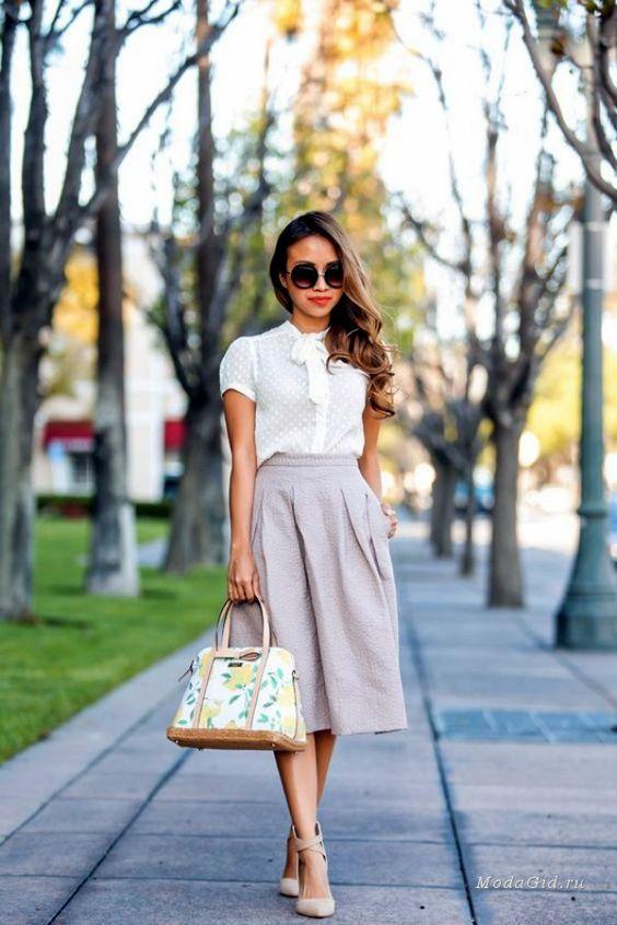 Женщина в белой блузке и серой юбке.