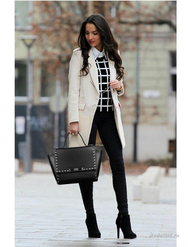 Бизнес-леди в стильном белом тренчкоте и черных брюках.