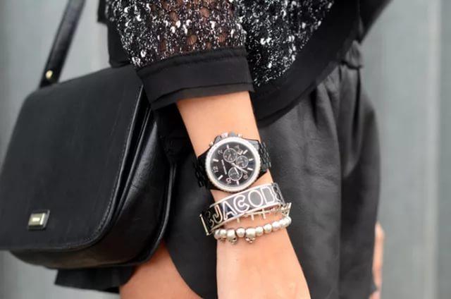 Часы, браслет и бусы на руке у девушки.