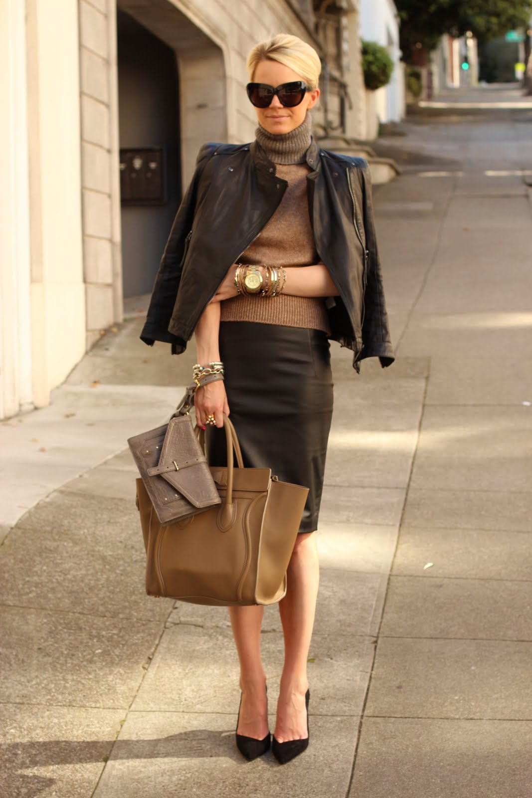 Женщина с часами, металлическими браслетами держит в руке сумки.