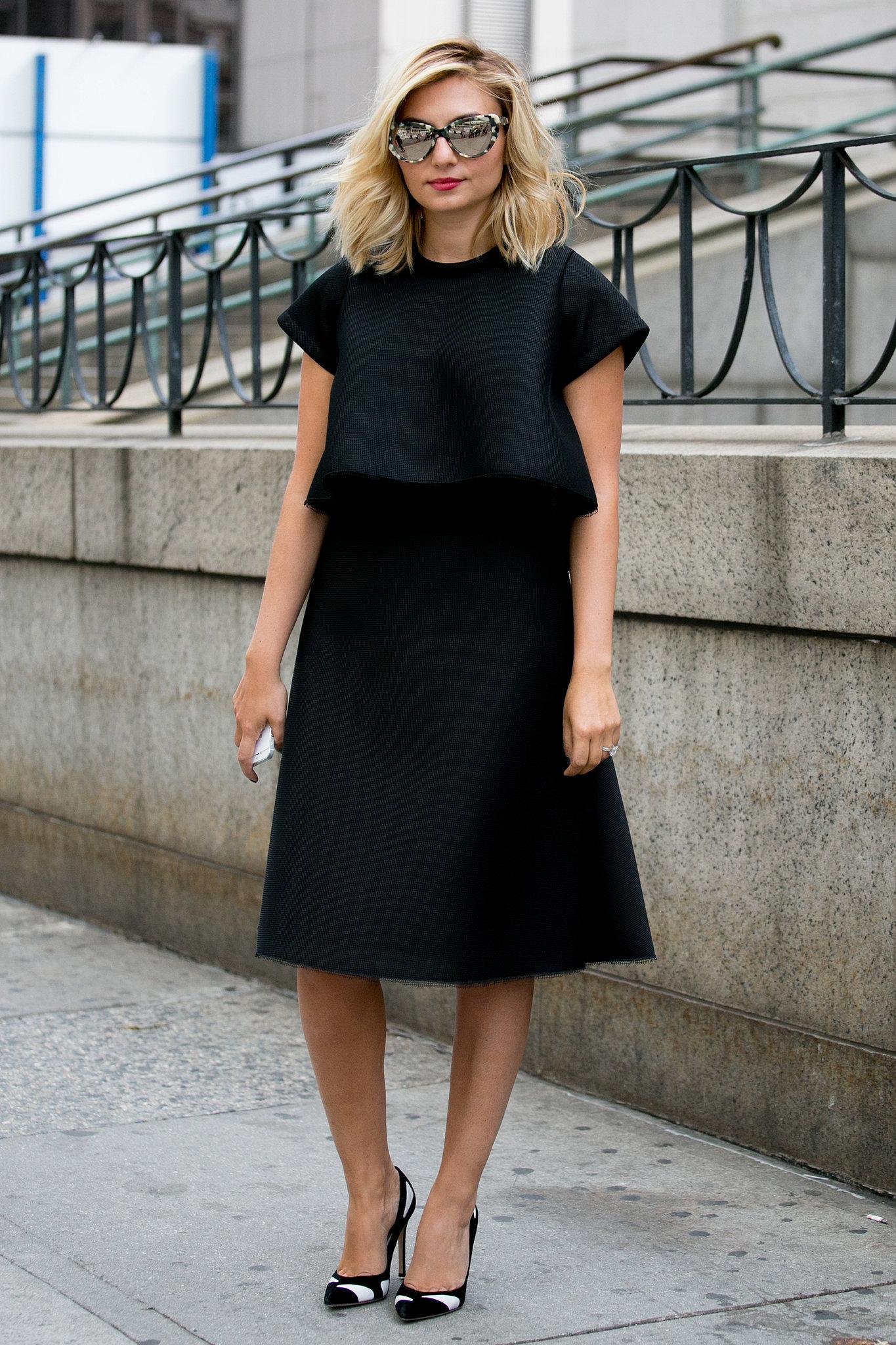 Женщина в черном платье и туфлях на высоком каблуке.