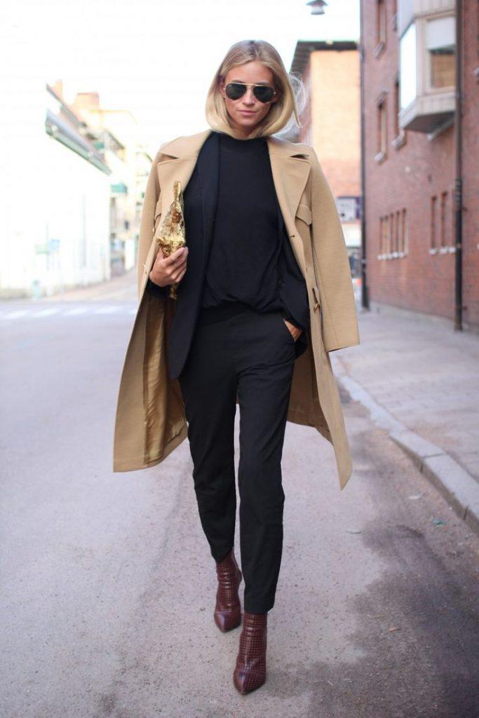 Женщина в черных брюках и бежевом пальто.