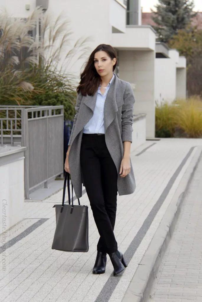 Бизнес леди в сером пальто и черных брюках.