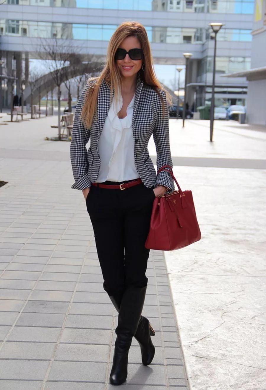 Бизнес леди в клетчатом кардигане и черных брюках с высокими кожаными сапогами.