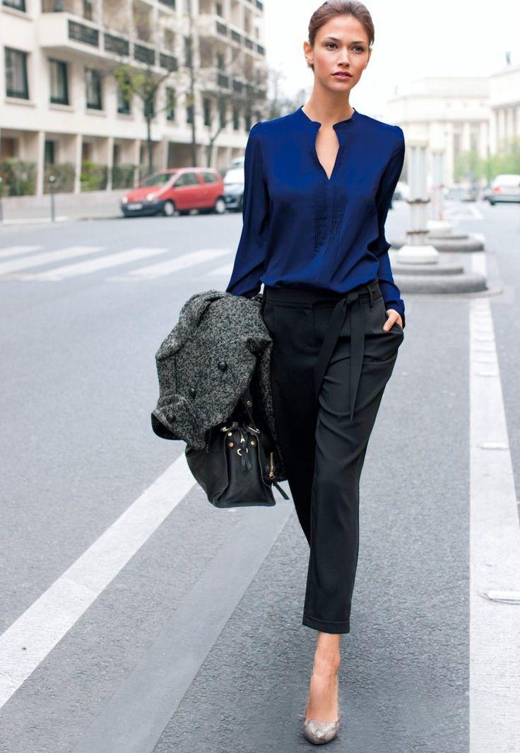 Бизнес леди в синей блузке и черных брюках.