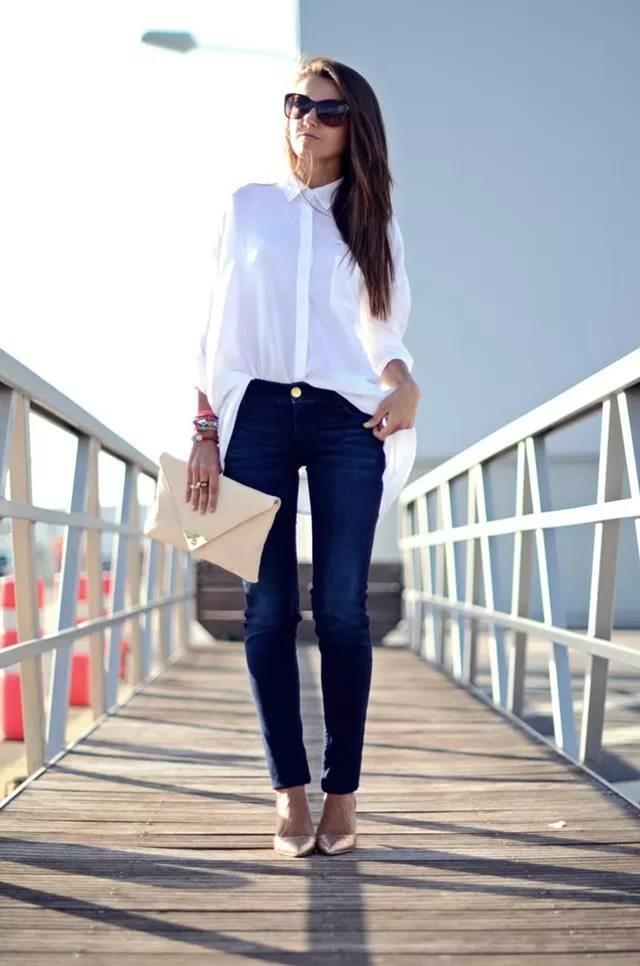 Женщина в белой рубашке и темно-синих джинсах.