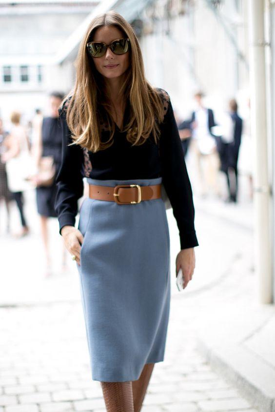 Женщина в юбке-карандаш и в черной блузке с V-образным вырезом.