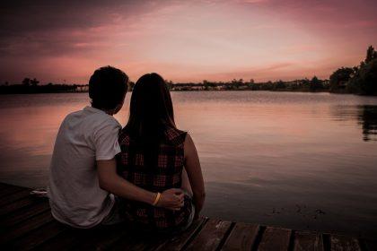 Парень с девушкой обнимаются, сидя на берегу.