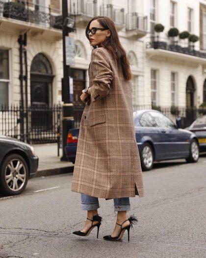 Женщина с подвернутыми джинсами и в туфлях на высоком каблуке.