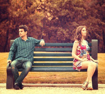Несовместимая пара сидит на скамейке порознь, отвернувшись друг от друга.