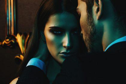 Женщина сексуально смотрит в объятиях мужчины, который хочет ее.