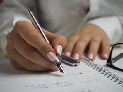 Девушка с розовым лаком на ногтях делает записи в тетради.
