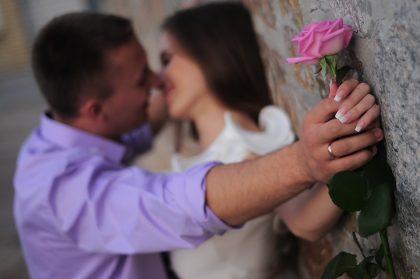 Мужчина прижимает женщину к стене и целует.