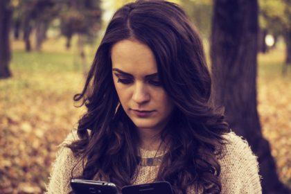 Девушка смотрит в телефон, ждет сообщение от парня, который ей не пишет.