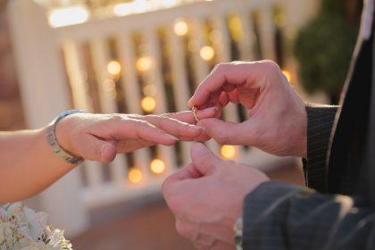 Мужчина надевает обручальное кольцо на палец женщине.