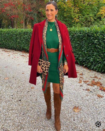 Женщина в зеленом платье, красном пальто и высоких сапогах.