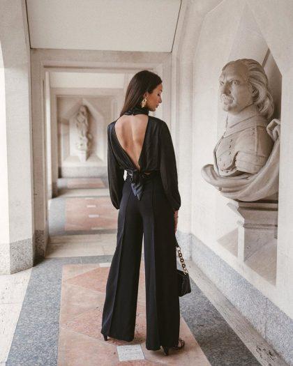 Женщина одета в строгий черный брючный комплект для похода в театр.