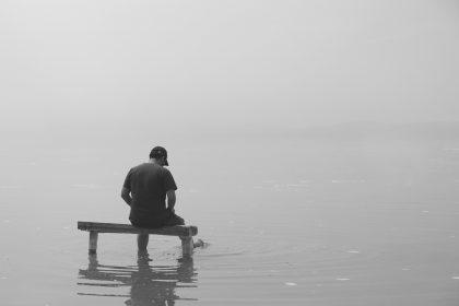 Человек сидит в тумане спиной, как во сне.